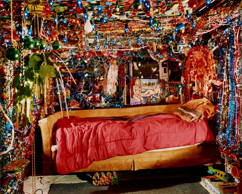 bed made on a gold upholstered couch under a low ceiling; walls and ceiling covered with strings of lights, tinsel and Christmas balls; painting of two nude women near head of bed/couch