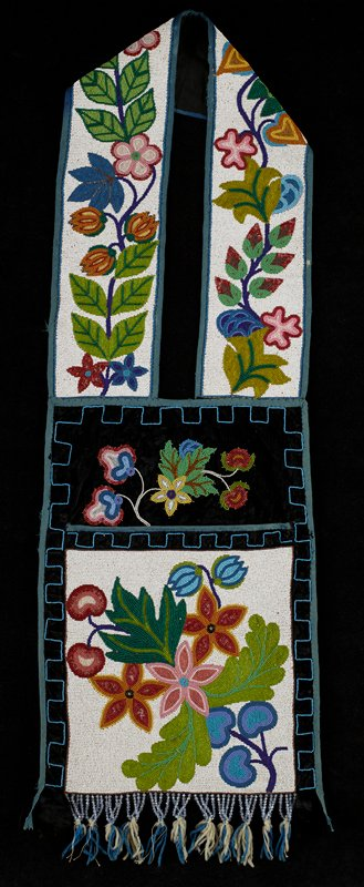 black and blue backing and trim; front of pouch and strap beaded overall with large, bright floral and leaf forms on white ground; beaded floral spray above pouch; blue squared-off linear border at pouch edges; transparent blue bead and blue yarn fringe