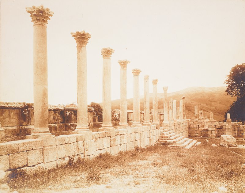 ruins with row of Corinthian columns on a stone wall; countryside in background