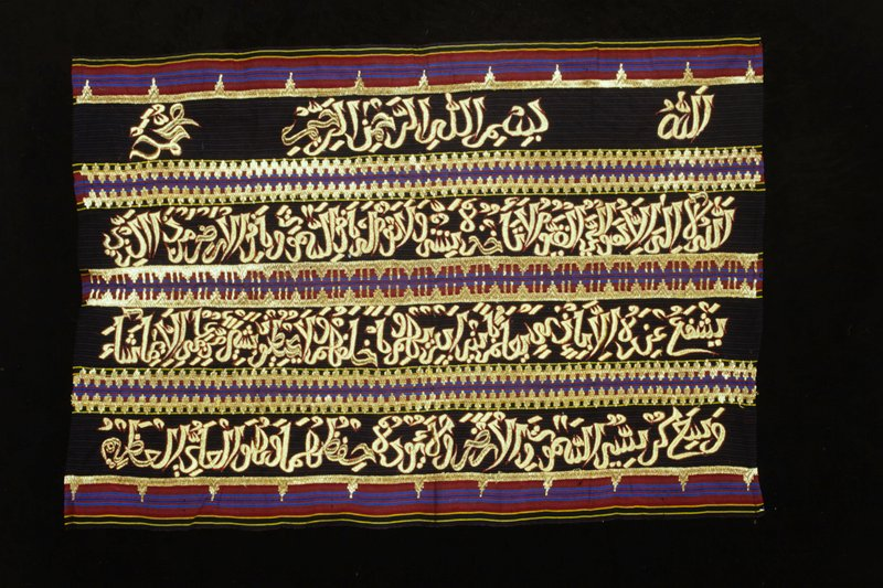 Fabric panel with multicolored stripes; sleeve sewn at back along one long side; 4 lines of Arabic text in gold embroidery bordered with red surrounded by gold embroidered decorative borders