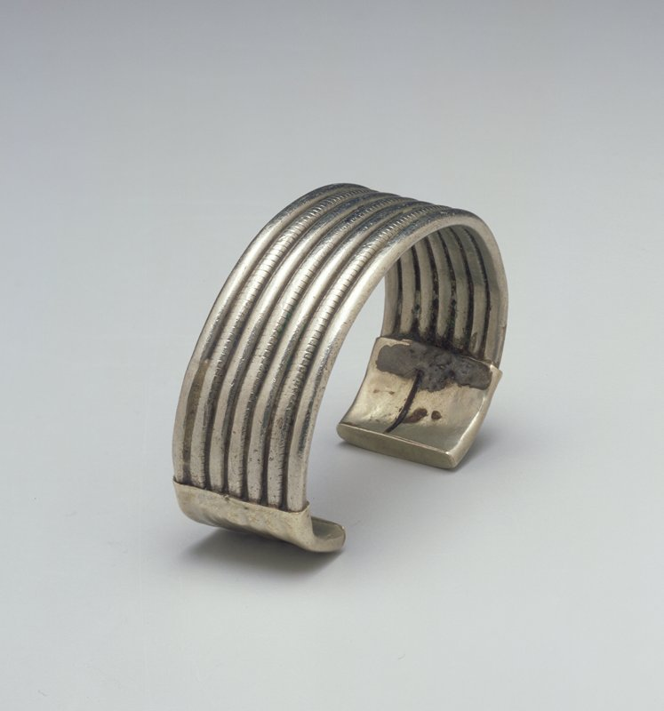 Bracelet with one open side; 7 thin wire bands (3 decorated with lightly incised lines) connected together; ends are capped with smooth silver sheets