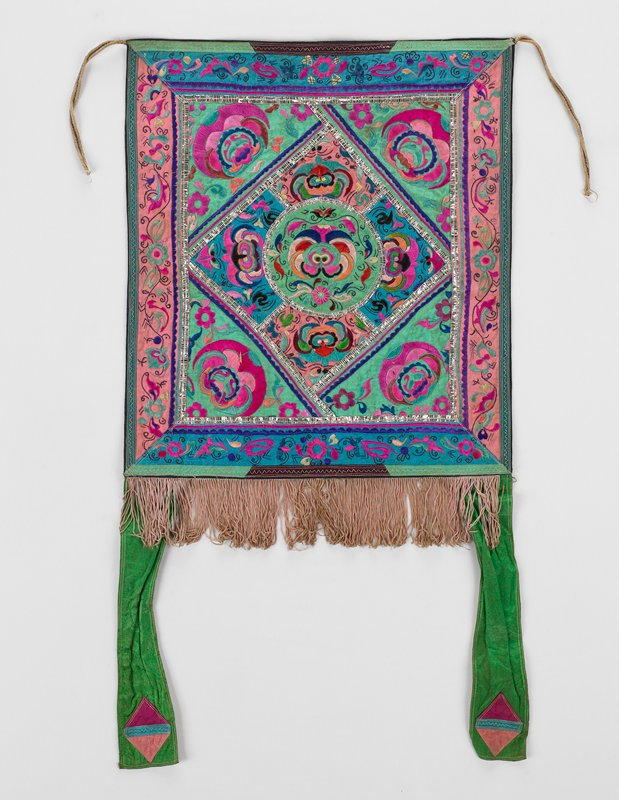 """diamond center of appliqued mask embroideries on pink, blue and green cotton and rayon (or silk?); same colors for borders and corner triangles; bottom edge has tan fringe and two 11-1/2"""" green straps with pink geometric designs on bottom; metallic tape outlines; black lining; three woven straps at top"""