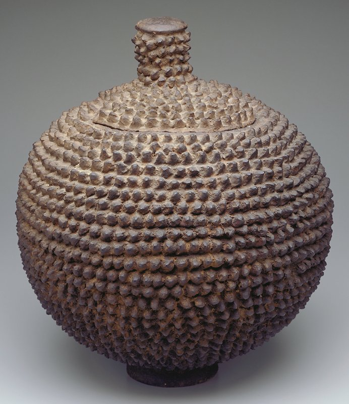 Round-bodied jar with small, short foot; opening for lid has 2 notches; lid has large knob; jar covered overall with rows of protruding nubs; nubs on lid and sides of knob