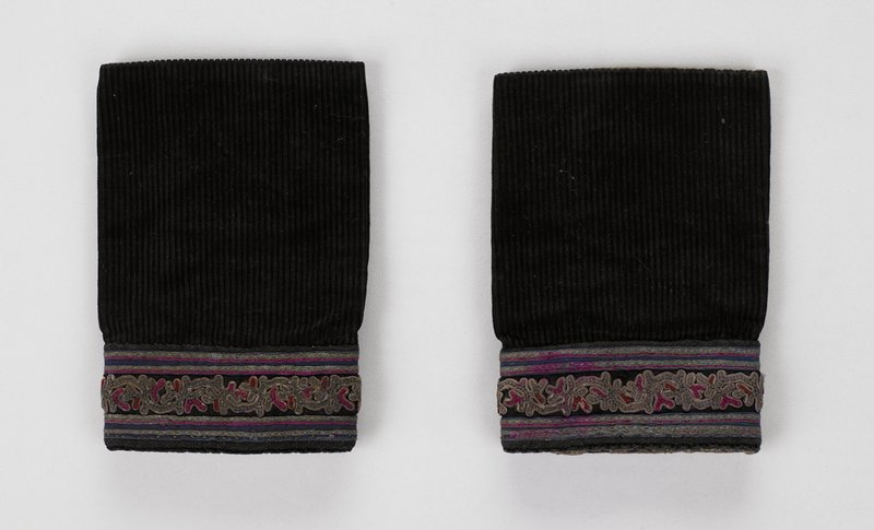 brown lined; narrow sleeve extensions in black corduroy with horizontal woven tape and embroidered lower edge