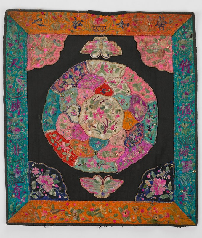black cotton center square has three elaborate rows of embroidered petals forming large flower with white center with bird embroidery; petals are pinks, greens, reds and dark blue; triangle corners in blue and pink silk appliques are similarly embroidered; butterfly appliques at top and bottom; borders of aqua and orange embroidered with Chinese symbols, flora and fauna; metal studs throughout; commercial printed lining; cotton with three snaps on bottom