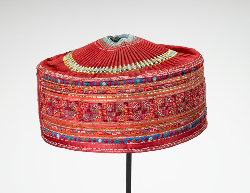pill-box style hat; red, blue and metallic; pleated top; corss stitch in red, orange and green on side; off-white lining