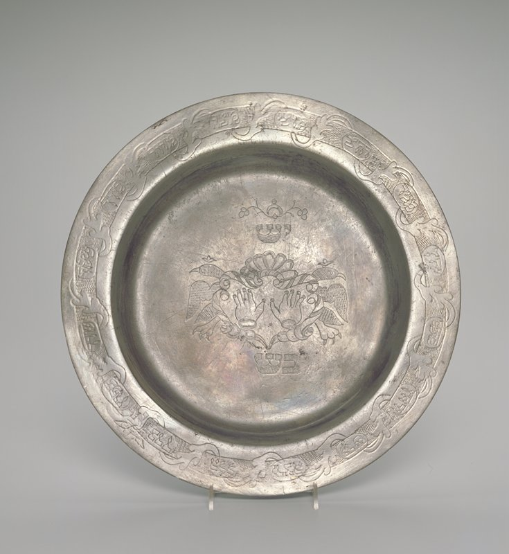 plate with flat rim; incised repeating organic design on rim with inscriptions inside ovals; interior incised with a pair of hands inside an organic element flanked by 2 birds facing outward