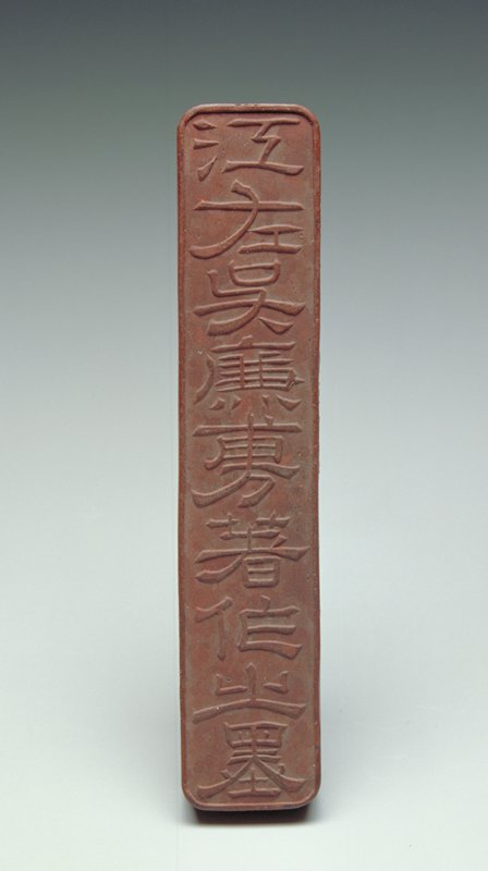rectangular form with rounded corners; incised inscription with traces of gilt on one side; relief inscription on opposite side; relief inscription on one long side and one short side