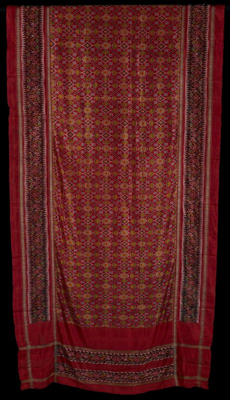 weft ikat; faux patola; red with two stripes of pattern along short ends, one along each length border; center is patterns of yellow, green and blue