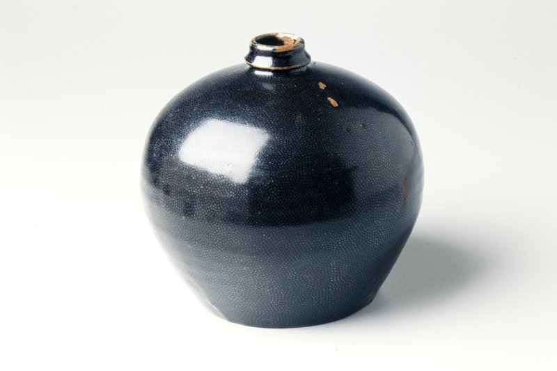 spherical jar with small conical neck rim and flat foot rim; black glaze with brownish areas at mouth; small, dull silver spots throughout glaze
