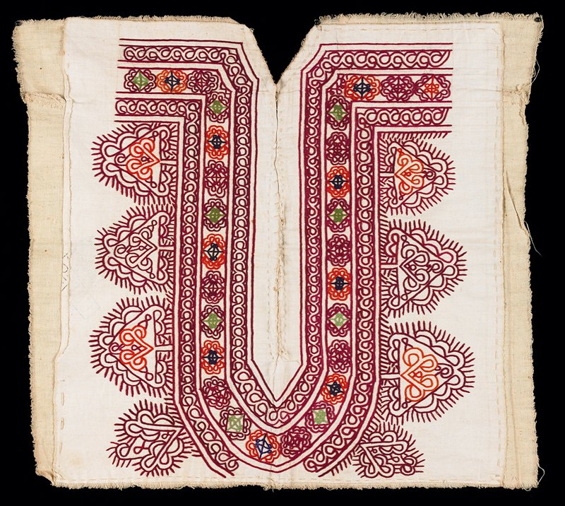 off white square with U-shaped design slit down center; chain stitch embroidery in somewhat Arabic style patterns; maroon, rust, blue, green; hand sewn to cotton backing; center slit is sewn together