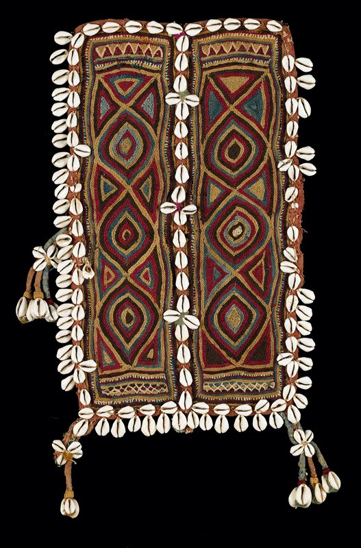 red, blue, tan wool chain stitch embroidery; two panels of three oval shapes divided by sewn-on white shells, which also surround entire panel; another row of shells hang freely from three sides: three fabric and shell tassels, two in center of long edge, two at short edge corners; embroidery applied to padded, gauze-like cotton