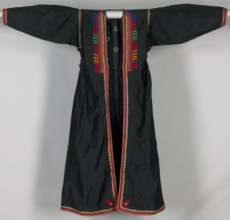 black cotton fitted to waist with flared bottom; open front, bottom edges, side openings and cuffs have woven red braid with gold rickrack; waist has red, orange, green and blue embroidery; skirt corners and underarms have embroidered designs and waist gatherings at sides; commercial print lining in waist; pleating at top of sleeves