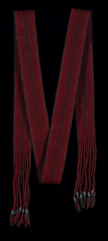 red and black with long, braided fringe both ends, ending with dyed wool and animal hair-wrapped tassels; heavy; coarse; woven in twill patterns; warp faced; Hepworth #193 sewn near one end