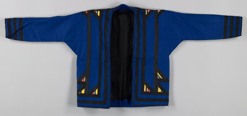 heavy blue cotton (?) flannel; open front; black woven braid on front, back and sleeves with multicolor triangular insets; black cotton lining with scalloped facing on inside