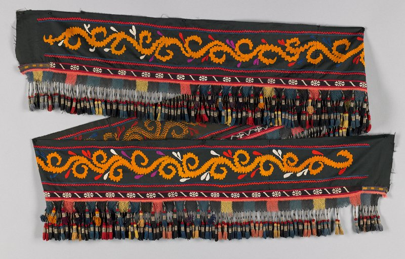 """black cotton with continuous gold scroll-like embroidery bordered within red and blue borders; below embroidered section is multicolor hand-knotted fishnet section with multiple 2-1/2"""" tassels wrapped with gold metallic thread; gold, blue, red, black, coral"""