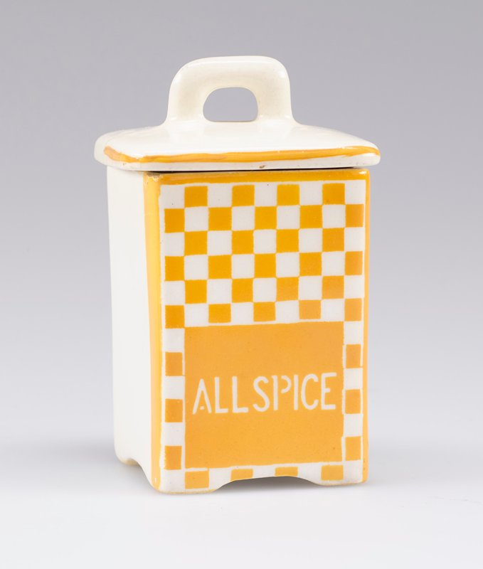 "small square container with cover with small handle; white porcelain decorated with yellow-orange checkerboard and ""ALLSPICE"" in white on front; stripe around edge of cover on front and sides"
