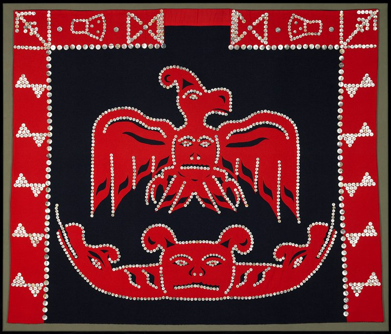 blue and red wool; bird design with human face on chest; pair of serpents heads with bear (or human?) face between them below bird; iridescent buttons highlight center design and form geometric designs at top and sides