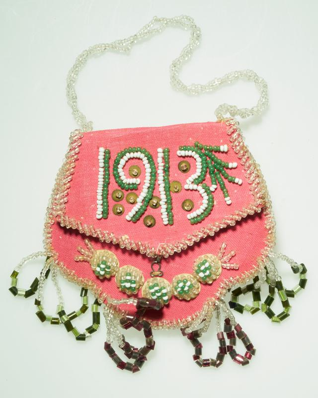 """pink front, red lining; clear, green and white beads; large raised flower motif on back, five small circular motifs on front; """"1913"""" on flap; four dangles (two green, two red) at bottom"""