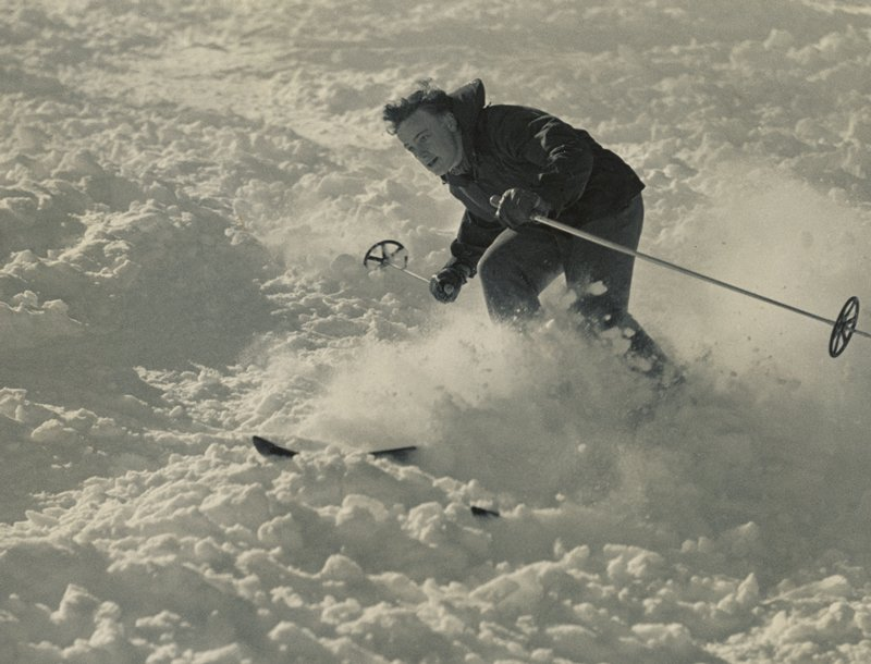 young man skiing down hill through heavy snow