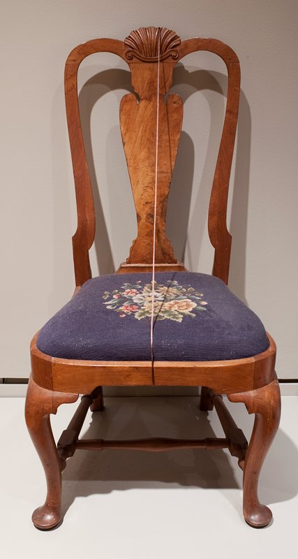 light wood curved backrest with shell motif at top center; curved front legs; embroidered seat cushion, dark blue with floral medallion in center