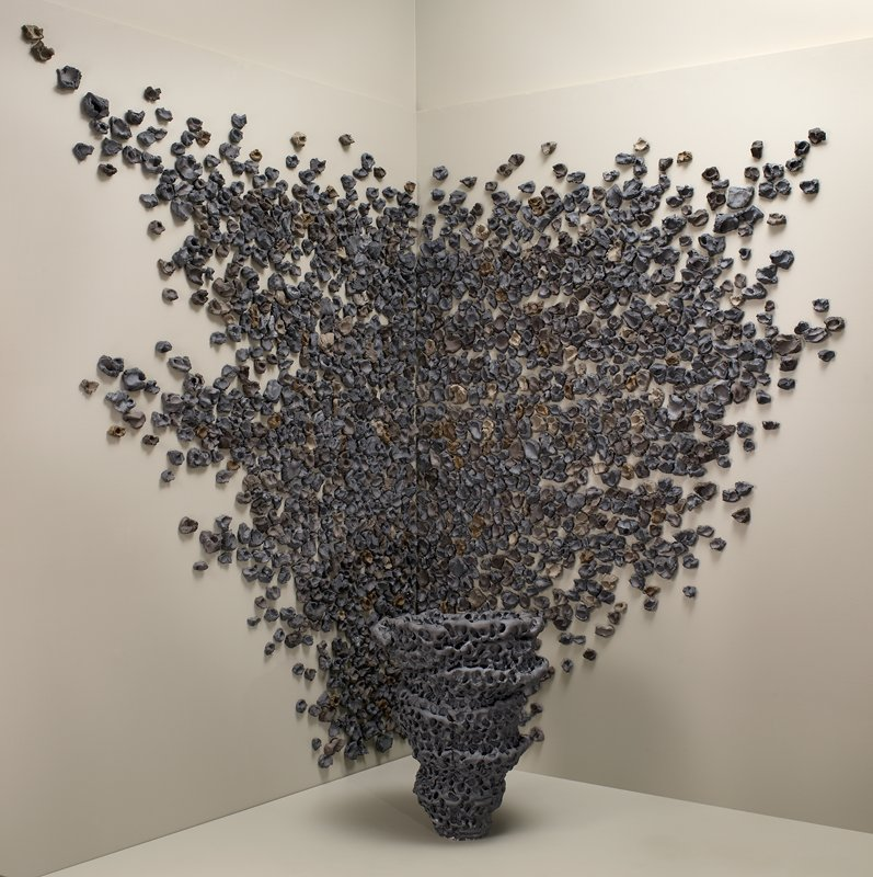 cone-shaped spiraling vessel in front of many lumps of clay affixed to wall; vessel is charcoal colored; clay bits are grey, charcoal, brown and tan; installation piece