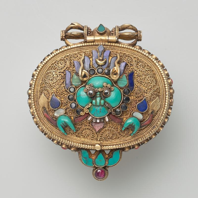 ovoid box with hinged cover; three raised characters on back; raised characters under cover; cover decorated with yali head on top, with various inlaid gems (primarily turquoise) and wire filigree; inlaid multicolred gems around edges of box; tara inside with turquoise inlay and gems on crown, holding filigree flowers