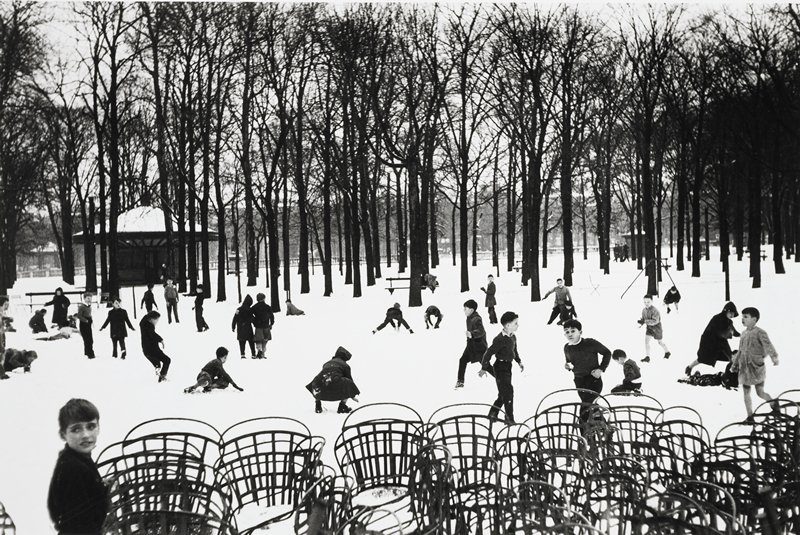 children playing in snow in middle ground; a jumble of chairs in foreground; trees and buildings in background
