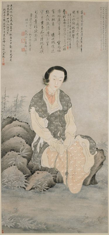 woman seated on rocks, wearing long vest-like garment in grey with stylized floral designs and a skirt with design of cranes in octagons; woman wears peal hoop earring; bamboo at left and right; text at top