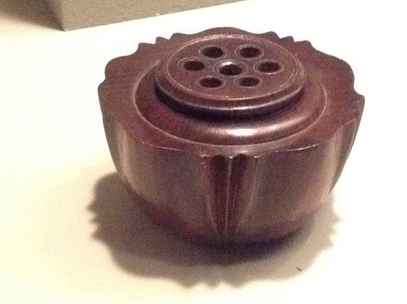 "round box with curved bottom; roughly shaped like a flower with five pairs of notches suggesting ""petals""; seven round holes in cover"