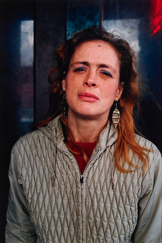portrait of a woman from mid-torso up; she is squinting at camera; wearing grey quilted jacket, large silver earrings, blue eye shadow and she has blue mark on her upper forehead; matted