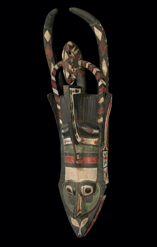 large animal's head with pointed mouth with zigzag teeth; two tall curved horns; elaborate openwork headpiece; decorated with red, white, blue, green and black pigments