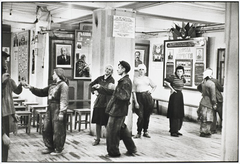 a group of workers, male and female, in a rough line across center ground; pictures, posters and notices on walls; a group of wooden stools at L behind people