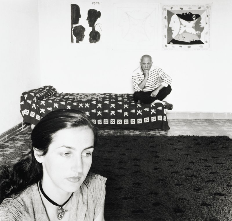 Picasso wearing a striped shirt and dark pants, seated at the foot of a bed in the corner of a room; three drawings on wall above Picasso's head; head and shoulders of a woman with long dark hair in LLC