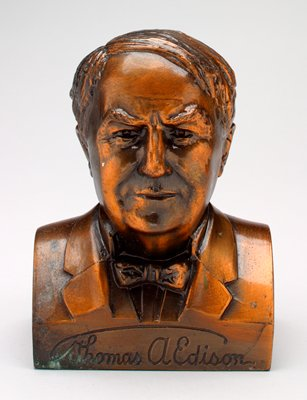 """bust of male figure wearing a bow tie; """"Thomas A. Edison"""" on bottom front; copper patina"""