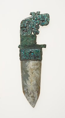 The tang is formed of the crested bird's head inlaid with turquoise. The socket, into which a jade blade has been fitted, is also inlaid with turquoise. A circular depression in the middle section of the tang suggests that it may also have once had inlay. Pieces of turquoise are missing in both tang and socket. The jade blade is dark, grayed-green mottled with cream and red toward the point on one side. The reverse is mottled with cream and red the length of the blade. Patina green