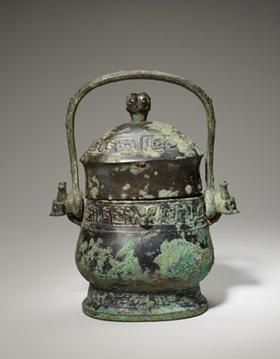 The form of this vessel is the usual broad type with oval section, but the exaggeratedly high collar of the lid, topped by a spherical knob, adds to the impression of height. The decor, disposed in three belts foot, neck, and lid, displays dragons with S-shaped bodies, turned heads, and large S-shaped crests (or horns?). The neck belt is divided in two panels on the long side by a free animal's head, the foot and rim belts by very shallow lines in low relief representing flanges. The handle ends in animals' heads with bottle horns. For a discussion of this type of horn see Karlgren, number 17 (50.46.18ab). Patina green and blue-green.
