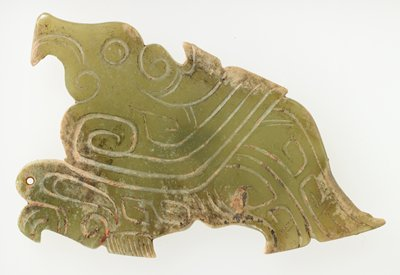 Pendant in seated bird silhouette, stylized incised with scroll design and indication of bird's detail on both sides identical. Translucent green jade; traces of red pigment and clay-like substance.