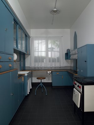 Kitchen cabinetry, sink, stool, lighting fixture; stool has three blue legs and wood seat; single-bulb light fixture is white enamelled on top and is saucer-shaped, bulb of light does not function; Siemens cookstove with small oven and two burners; 12 metal bins for dry staples; one large metal scrap bin