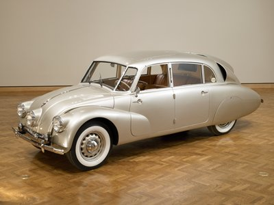 silver four-door automobile; front in the style of a Volkswagen with three headlights; sloped back with back central vertical fin and back louvered window; brown leather interior; sunroof